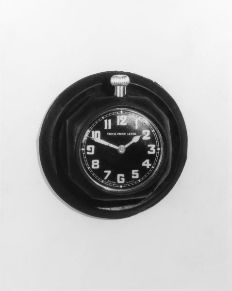 A shock proof car clock (with luminous figures), which adheres to the dashboard by means of its rubber casing. Only 7 shillings and 9 pence from Harrods of London. Date: 1930s