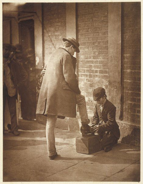 A Shoe-Black boy cleans and shines a gentleman's shoes on a wooden block