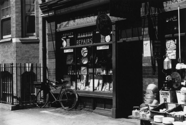 The front window of A. Marsh & Son's shoe repair shop is full of goods such as leather soles, polish and heel grips. A delivery bicycle is parked outside. Date: 1930s