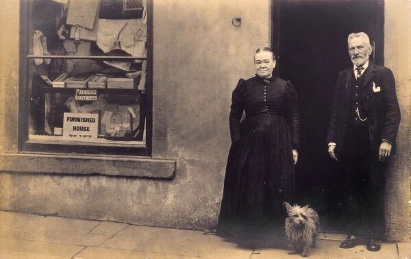 A dog stands with its master and mistress outside a shop which is located in a private home, the goods in the window indicating the nature of the business