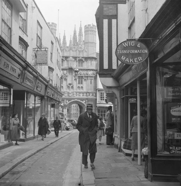 A n old shopping street in Chester, featuring, along with other retailers, a wig seller! The Cathedral can be seen in the background. Photograph by Norman Synge Waller Budd