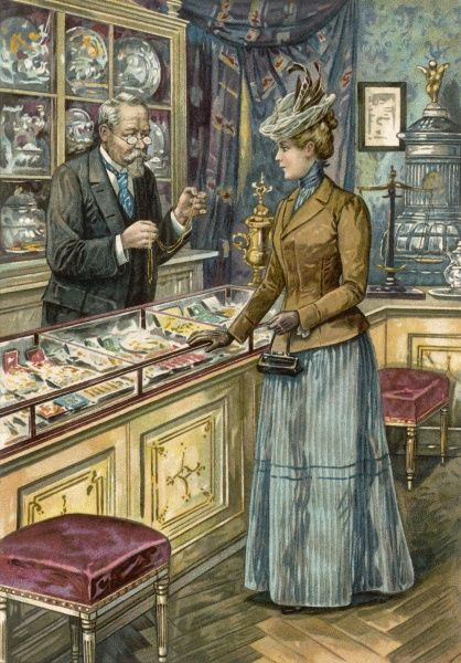 A jeweller holds up a fine gold necklace for a lady to examine