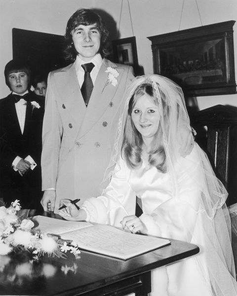 A young bride and groom sign the register. The groom is wearing a suit with very wide lapels and the bride wears a satin wedding dress with fur around the cuffs