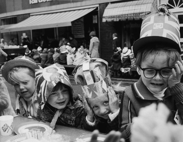 ELIZABETH II'S SILVER JUBILEE A children's tea party in a street in Horley. One girl has a picture of the Queen on her hat. Another wears a crown