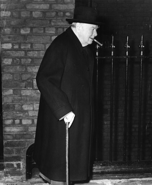 Sir Winston Leonard Spencer Churchill (1874-1965) British politician and Prime Minister smoking a cigar with a walking stick leaving his London residence for Chartwell three days before his 85th birthday
