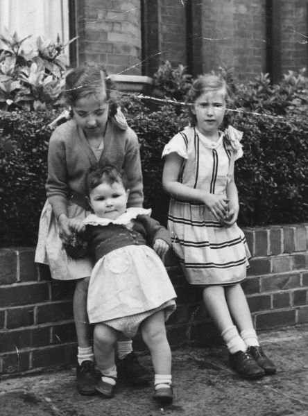 Three sisters sitting on a front garden wall in a street of Victorian terraced houses