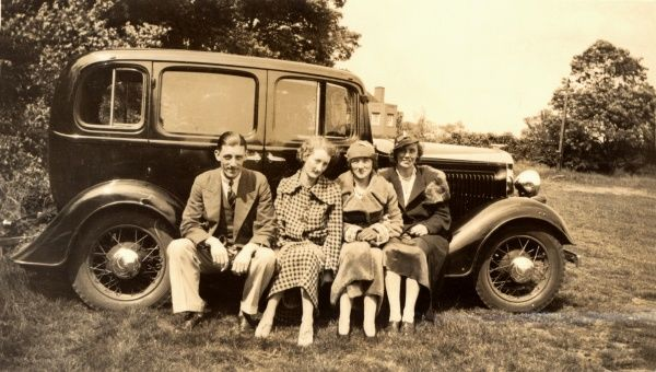 A gentleman and his three lady companions sit on the running board of their small car (a Vauxhall 12 Six Light Saloon) in a field