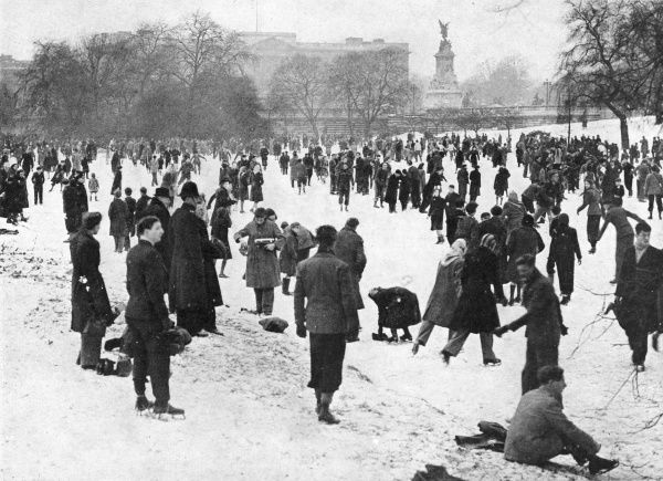 A cheerful crowd disporting on the ice in front of Buckingham Palace. During one of the coldest winters experienced by Britain, nearly all London lakes were available for skaters, with big crowds turning out on the Serpentine, on the Round Pond