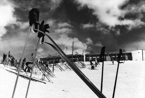 Skiing gloves, poles and skis, but no skier? On the snow slopes above Zermatt, Switzerland, with the Rack Railway behind. Date: 1960s