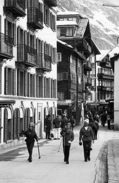 Skiers walking through the town of Zermatt, Switzerland. Date: 1960s