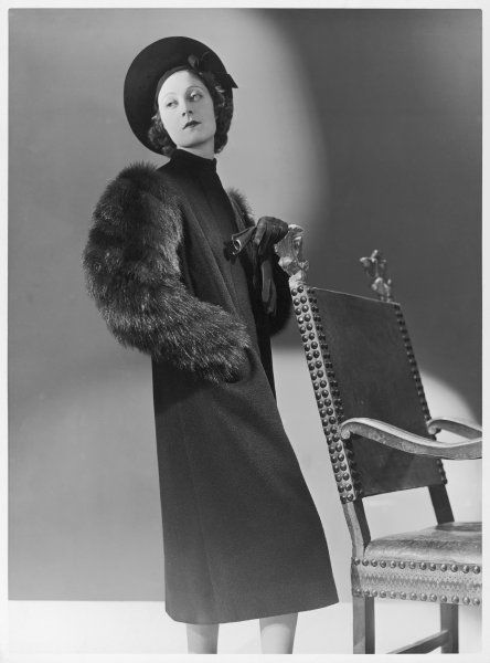 A three-quarter length coat by Bruyere in black wool with skunk fur sleeves. The model wears a hat with a wide up-turned brim which frames her face