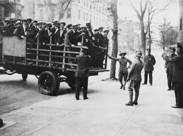 A truck load of men in boaters who were picked up without registration cards, exempting them from conscription into the U.S army in WW1. They were rounded up, then taken to Armory for examination