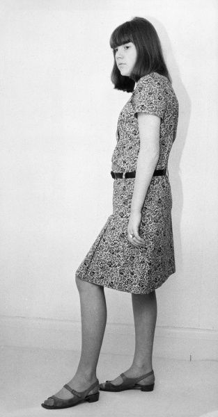 A girl wears a shapeless low waisted dress in a floral print & narrow contrasting belt & suede sling-back peep toe sandals. Her hair is cut in a long bob with a fringe. Date: 1960