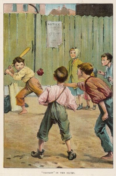 A group of boys play a game of cricket on waste ground. A piece of wood propped up with coats serves as a makeshift wicket, while the ball is composed of who knows what?