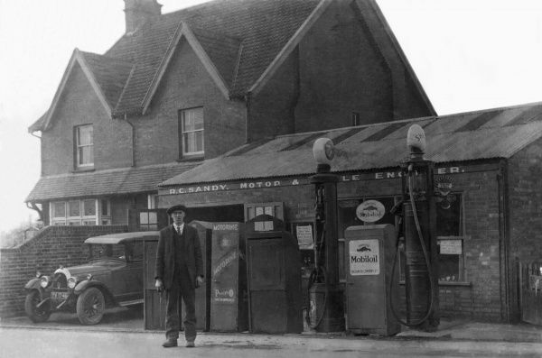 A pump attendant stands by the petrol pump at this local country garage