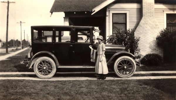Lady standing alongside an unidentifed small family car, parked on a driveway