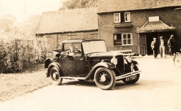 A small half-convertible Austin 10 Cabriolet with the rear soft-top roof open, parked in front of a country pub with the proud owner at the wheel