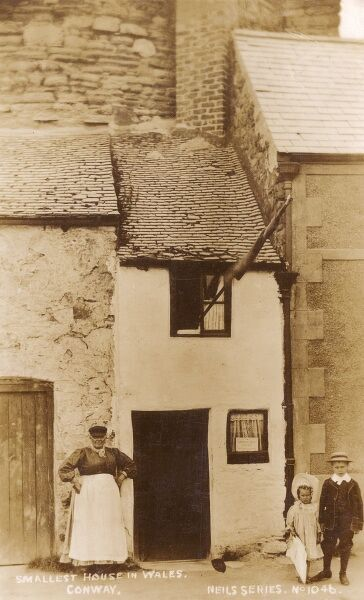 The smallest house in Great Britain, also known as the Quay House, now a tourist attraction on the quay in Conwy, Wales. An extremely formitable Welsh lady stands outside, possibly the guardian of the property, which has not been occupied since 1900