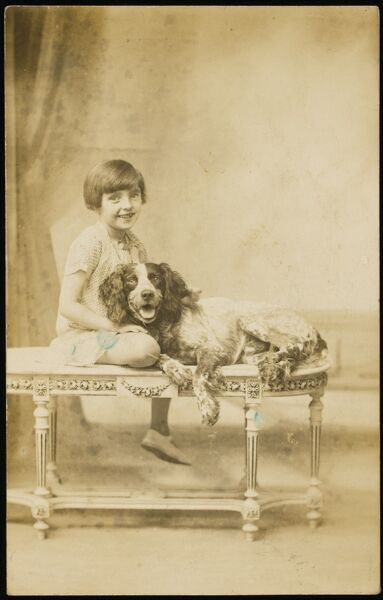 A smiling, jolly little girl, poses on a decorative table with her equally happy English Springer Spaniel pet dog