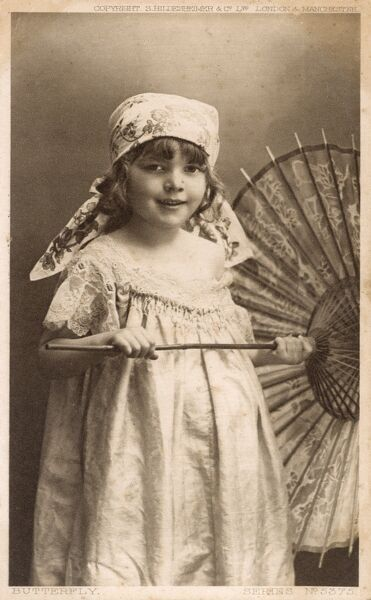 "A young girl with a Japanese parasol. She is wearing a headscarf and seemingly wearing a nightie, but this does not totally explain the slightly baffling card title: ""Butterfly"".... Date: circa 1910s"