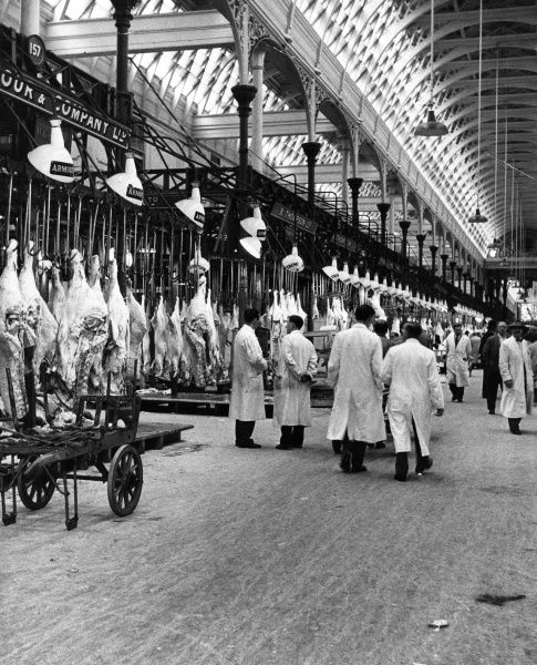 Carcasses hanging from hooks and butchers wearing their traditional white overalls at Smithfield Market, London. Date: 1950s