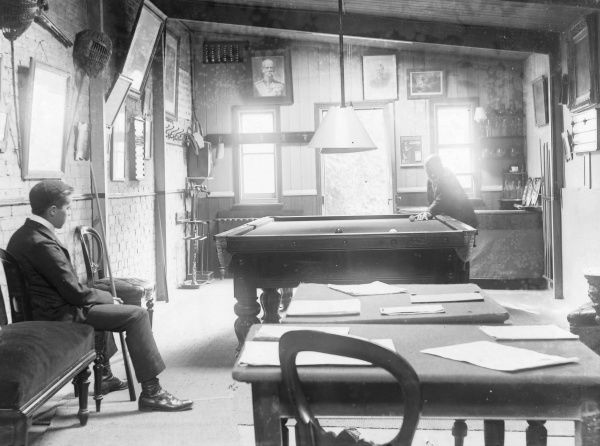 View inside a snooker room, with two players. One player is aiming with his cue, while the other player sits waiting for his turn. In the foreground are two small tables with papers set out on them, and a gas lamp above