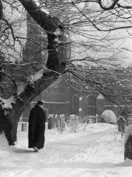 Not a ghost, just the village Vicar trudging through the snow for the 8 a.m. Morning Communion at Buckden, Cambridgeshire, England. Date: 1950s