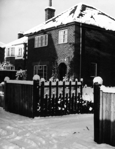 Suburban houses covered in winter snow. Date: 1960s