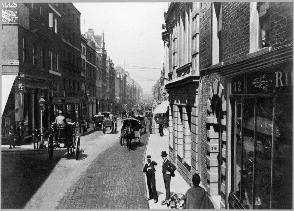 Two young men, one shading his eyes from the sun and the other with his hands on his hips, stand in Bond Street in the days of horse-drawn traffic