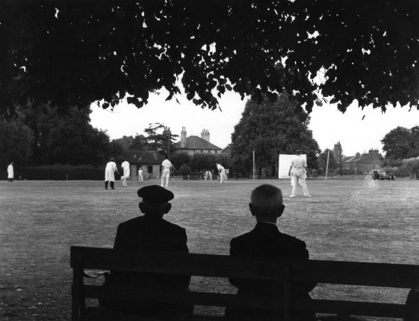 Two men sit on a bench in the shade to watch a cricket match in Kent Date: 1950s