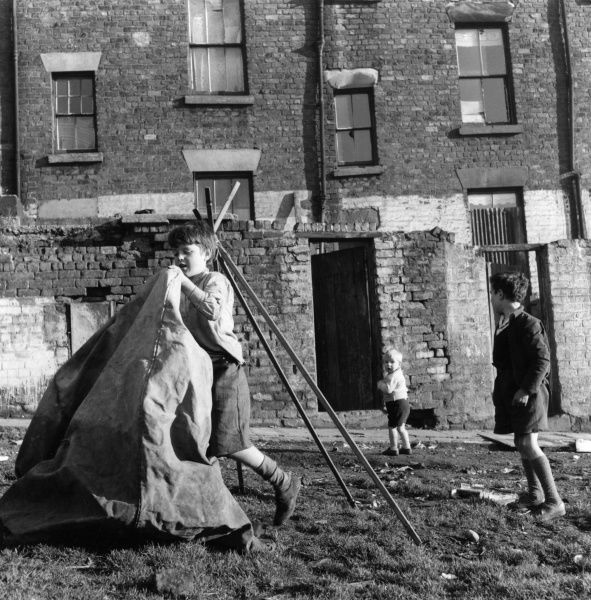 Children making a tent in front of a row of terraced houses in Liverpool Date: 1960s