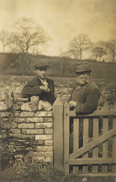 Typical English farming folk: a young man and an old man look at the photographer from the other side of a gate