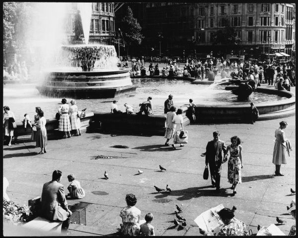 People relaxing in Trafalgar Square on a warm summer evening; women in summer dresses and lots of children feeding pigeons and playing