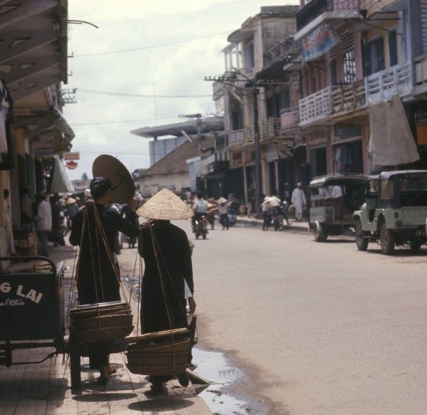 People in one of the major shopping streets at Hue, South Vietnam. Date: 1976