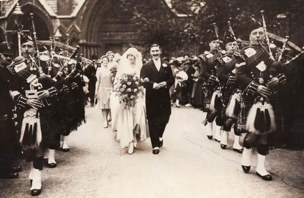 A society wedding between Lieutenant-Colonel Archibald Vivian Campbell Douglas and Elizabeth Cicely de Bunsen. The bridegroom is from Mains, Laraich, Aberfoyle, Stirlingshire, Scotland. The happy couple are piped out of the church by Scots Pipers