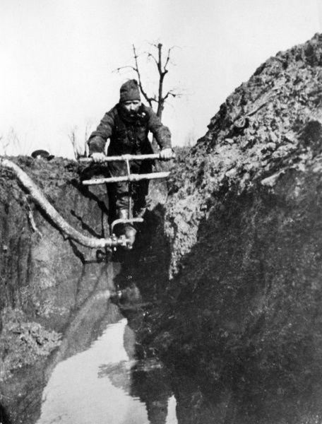 A soldier in a water-filled trench on the Western Front (possibly near Ypres) during the First World War. The equipment he is using is probably for pumping out the water. Date: 1914-1918
