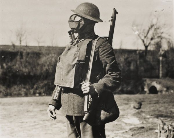 British soldier wearing a gas mask and helmet on the Western Front in France during World War I in 1918
