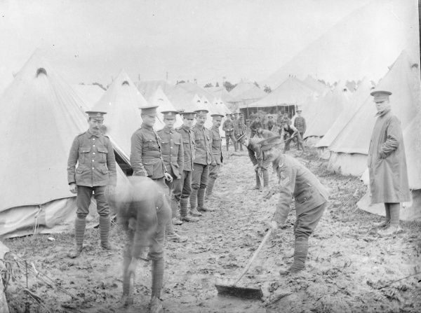 A group of soldiers belonging to the Brecknockshire Battalion South Wales Borderers, cleaning up at a rather muddy training camp
