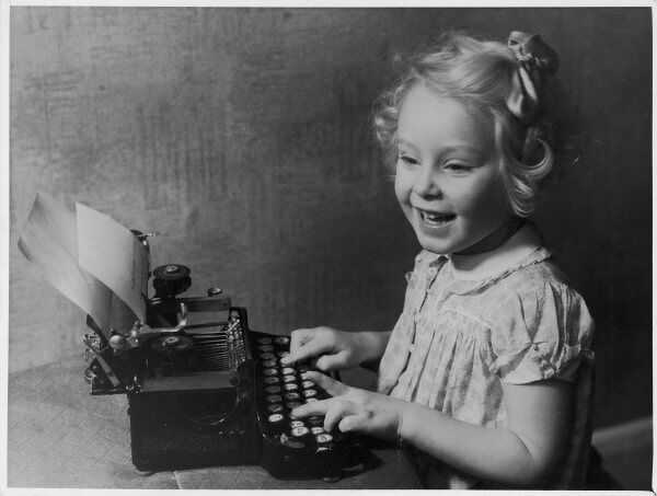 A little girl pretends to write on a typewriter