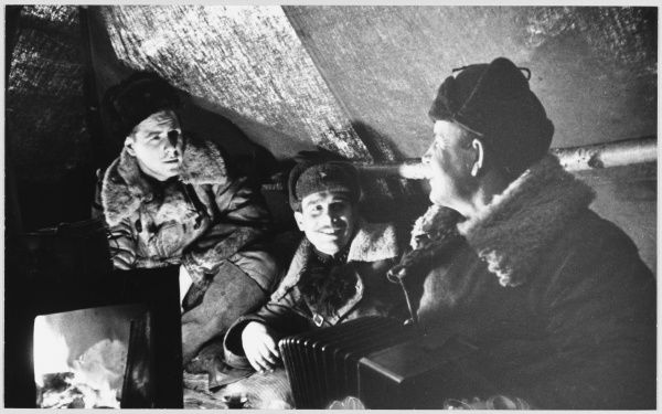 Soviet soldiers entertain themselves in a dug-out