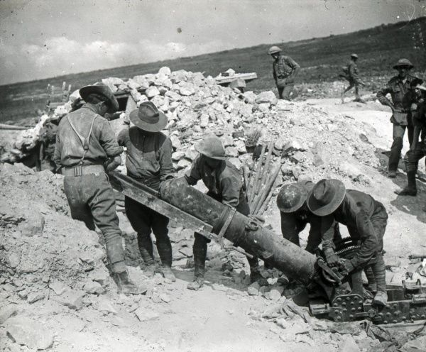 A group of soldiers in a dry and dusty landscape, loading a large field gun during the First World War