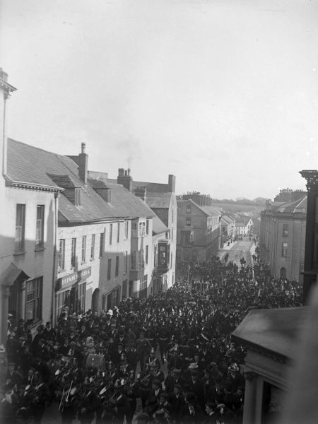 Soldiers marching up the High Street in Haverfordwest, Pembrokeshire, Dyfed, South Wales, watched by various townspeople, around the time of the outbreak of the First World War. A band of musicians can be seen in the foreground