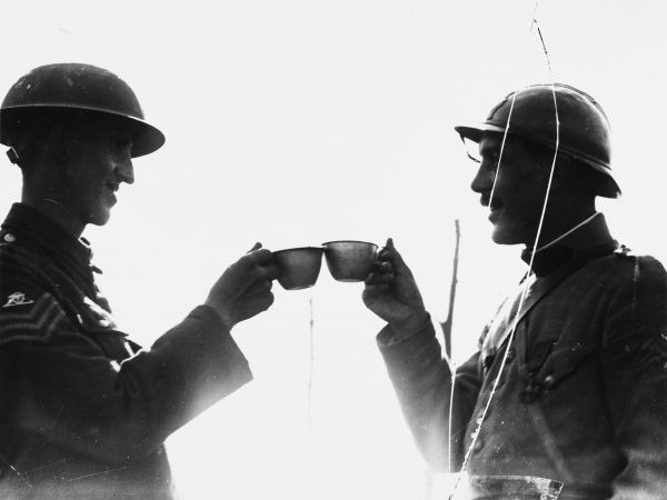 A French and a British Royal Garrison Artillery (RGA) sergeant toasting each other at Boesinghe in Belgium on the British front during World War I on 18th August 1917