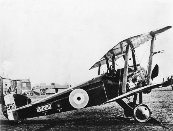 A Sopwith Camel biplane of No. 17 Aero Squadron USAS (United States Air Service) on an airfield during the First World War. Men can be seen in the background on the left, sitting outside a hut.  1916-1918