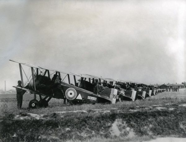 A long line of Sopwith Camel biplanes of No. 148 Aero Squadron USAS (United States Air Service) on an airfield during the First World War, with pilots and ground crew. Date: 8 August 1918