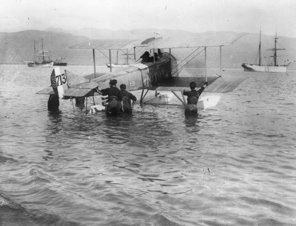A Sopwith seaplane about to set off on a flight on the Balkan Front during the First World War. Seen here with the pilot in the cockpit and men wading in the sea around it. Date: 1914-1918