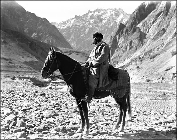 A Turkic man sat on a mighty steed in a mountain pass in the far north of India or the very south of Xinjiang Province, China on the road through the mountains to Kashgar. Photograph by Ralph Ponsonby Watts