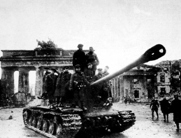 Photograph showing a Soviet heavy tank moving through Berlin, with the Brandenburg Gate in the background, May 1945. Berlin fell to the Russian Army on 2nd May 1945, after a battle which lasted 17 days. Given the demeanour of the men riding on the tank
