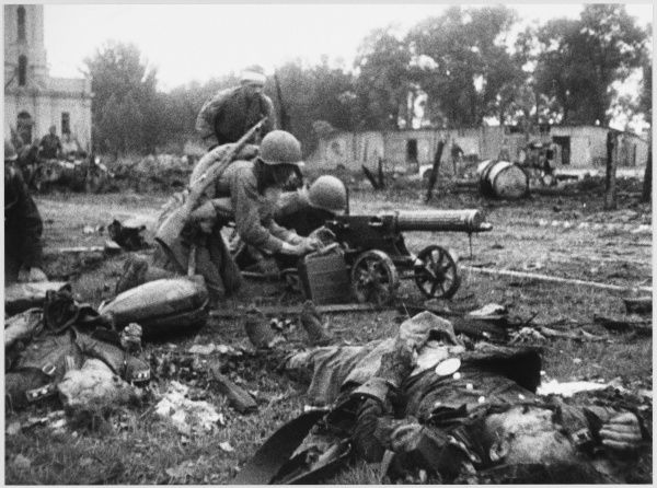Soviet machine gunners in action during street fighting, regardless of the corpse lying beside them