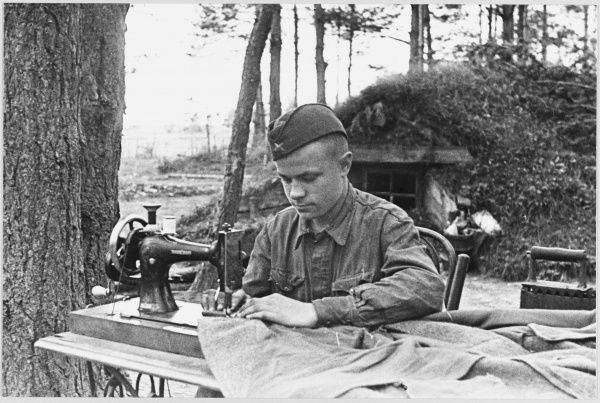 A Soviet tailor at work near the front, with his sewing machine set up on a table